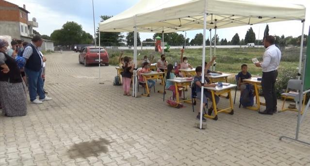 Okulun yakınında bulunan Yeniimaret Mahallesi'nin meydanına temin ettiği çadırı kuran ve okuldan masaları taşıyan Müdür Çekiç, öğrencilere açık havada ders anlatmaya başladı.